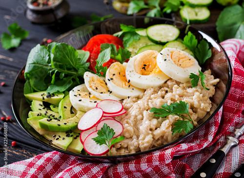 Foto Murales Healthy salad of fresh vegetables - tomatoes, avocado, cucumber, radish, egg, arugula and oatmeal on bowl. Diet food.