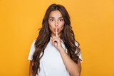 Emotional young pretty woman posing isolated over yellow background showing silence gesture.