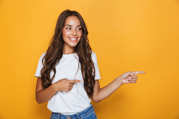 Young pretty woman posing isolated over yellow background showing copyspace.