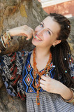 Happy smiling indie style woman with dreads, dressed in boho style ornamental dress outdoor