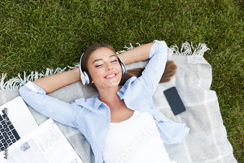 Fototapeta Beautiful young pretty woman in park outdoors listening music.