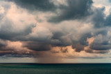 Rain clouds tightened the whole sky above the sea at sunset - 225656301