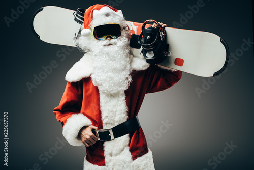 serious santa claus in ski mask standing with snowboard over shoulder isolated on grey background