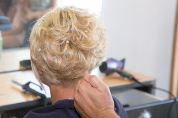 Beautiful blonde girl receving by an professional evening hairdress in a beauty salon © sylv1rob1