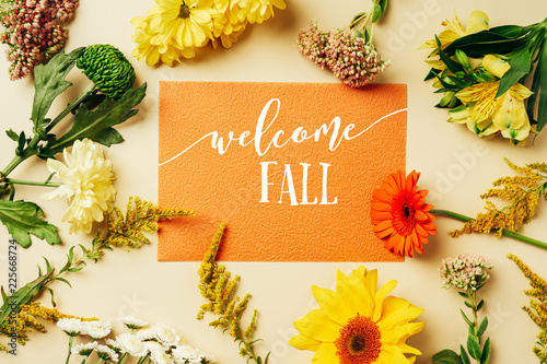 "Leinwanddruck Bild flat lay with various wildflowers around orange card with ""welcome fall"" lettering on beige background"