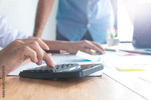 Side view of the accountant hand. He uses a calculator and writes numbers. Accounting concepts © jariyawat