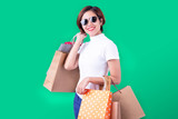 Portrait of an excited beautiful asian girl wearing dress and sunglasses holding shopping bags isolated on green background - 225675989