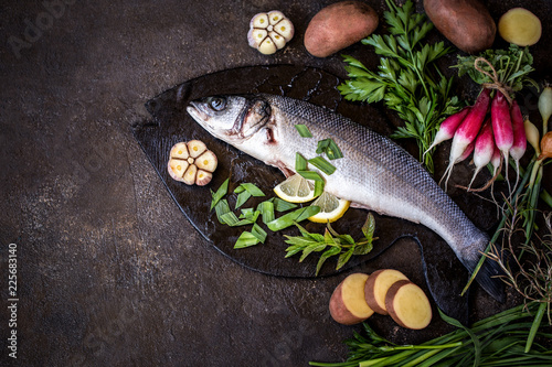 Sticker fish sea bass with vegetables potatoes, garlic and herbs, ingredients for cooking