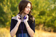 Leinwanddruck Bild - portrait of a beautiful girl witn headphones on her neck, young woman listening to music on nature