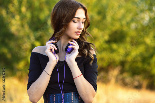 Leinwanddruck Bild portrait of a beautiful girl witn headphones on her neck, young woman listening to music on nature