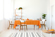 Leinwanddruck Bild - Long dining room table covered with orange tablecloth and comfortable white chairs around it.