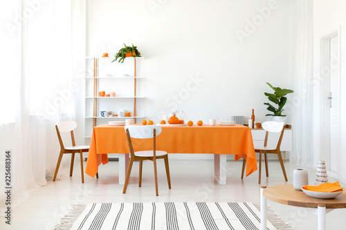 Leinwanddruck Bild Long dining room table covered with orange tablecloth and comfortable white chairs around it.