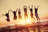 Group of happy friends jumps in sunset water - 225689306
