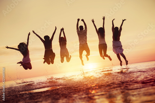 Group of happy friends jumps in sunset water © cppzone