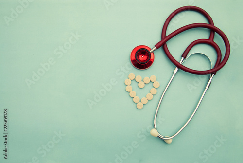 Red stethoscope with tablets, pills on blue background. Copy space. Medicine, heartbeast concept. © Inga