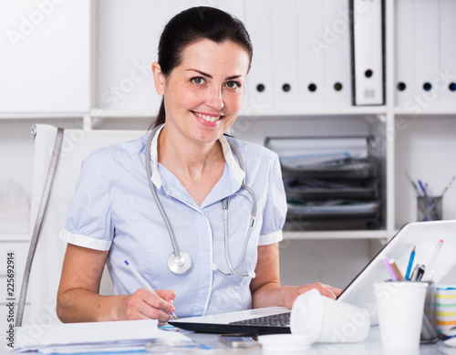Foto Murales Medical worker with stethoscope writing recipe