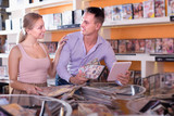 Cheerful family couple selecting erotic video in shop