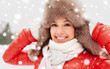 Quadro people, season and leisure concept - happy woman in winter fur hat outdoors
