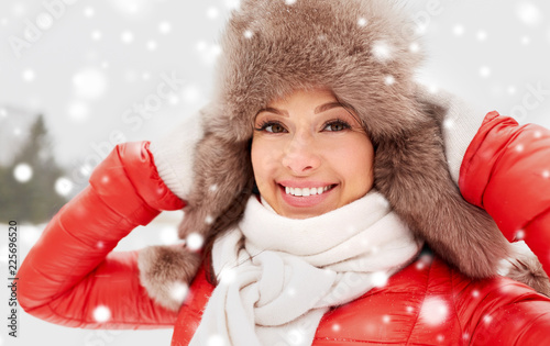 people, season and leisure concept - happy woman in winter fur hat outdoors - 225696520