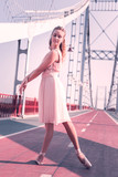 Grace and beauty. Beautiful nice woman performing a dance while standing on the bridge