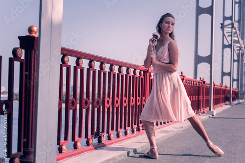 Tender beauty. Pleasant attractive ballerina standing with a flower while being on the bridge - 225710715