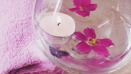 Romantic composition with a candle and violet flowers floating in a bowl of water.The concept of Spa,cosmetic,procedure,treatment.