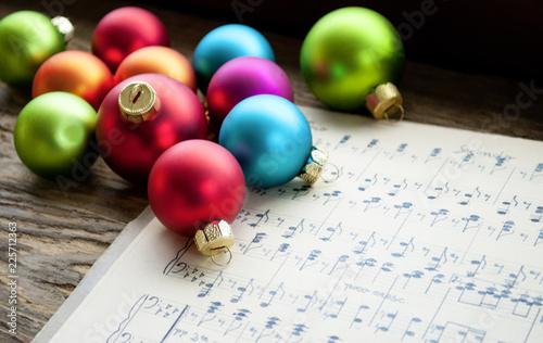 Leinwandbild Motiv Altes handgeschriebenes Notenblatt mit vielen bunten Weihnachtskugeln, Weihnachten, xmas
