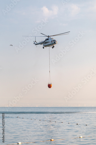 Fototapeta A helicopter of the fire service with a fire fighting bucket is taking part in putting out a fire. A helicopter with a red basket is lowered over the sea to catch water.