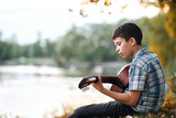 the boy plays an acoustic guitar, sits on the Bank of the river, autumn forest at sunset, beautiful nature and the reflection of trees in the water