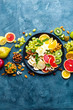 Leinwanddruck Bild - Healthy vegetarian bowl dish with fresh fruits and nuts. Plate with raw apple, orange, grapefruit, banana, kiwi, lemon, grape, almond, hazelnut and cashew nuts. Healthy balanced eating