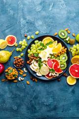 Healthy vegetarian bowl dish with fresh fruits and nuts. Plate with raw apple, orange, grapefruit, banana, kiwi, lemon, grape, almond, hazelnut and cashew nuts. Healthy balanced eating