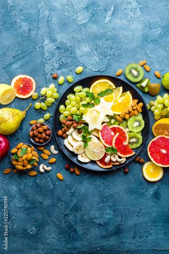 Leinwandbild Motiv Healthy vegetarian bowl dish with fresh fruits and nuts. Plate with raw apple, orange, grapefruit, banana, kiwi, lemon, grape, almond, hazelnut and cashew nuts. Healthy balanced eating