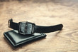 Wristwatch and wallet on wooden background. - 225741757