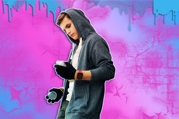 New paint. Attentive young talented street artist wearing casual clothes and having hood on his head while looking at the new spray paint
