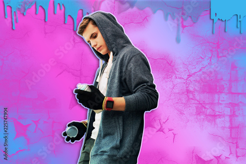 New paint. Attentive young talented street artist wearing casual clothes and having hood on his head while looking at the new spray paint - 225747904