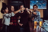 Group of happy multiracial friends making a toast with vodka while standing at bar or pub. - 225752536
