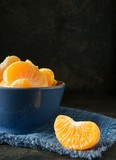 A blue bowl of orange tangerine segments against a dark rustic background with copy space for your text