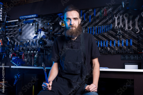 Leinwanddruck Bild Portrait of small business owner of young man with beard. Guy bicycle mechanic workshop worker sitting with tool in his hand in a working black clothes in an apron in the background of a bicycle shop.