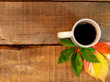 Cup of coffee near some autumn leaves on a rustic barn wood background.