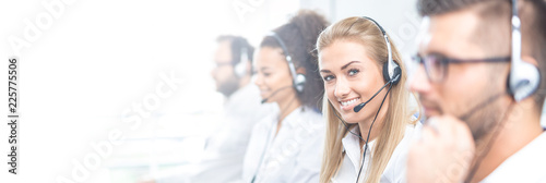 Leinwanddruck Bild Call center worker accompanied by her team.