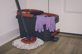 Cleaning tools: flat wet-mop  and  bucket with violet gloves on parquet floor. Close up.  Toned photo. - 225780595