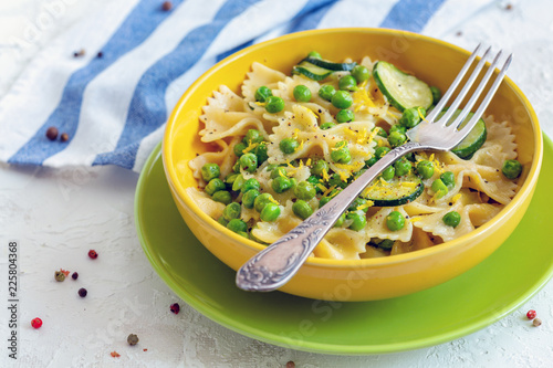 Foto Murales Traditional Farfalle pasta with zucchini and green peas.