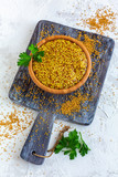 Bowl with grain mustard and a sprig of parsley. - 225804558