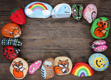 Border of Colorful Cartoon Hand Painted Animal Rocks on Wood Background - 225804934