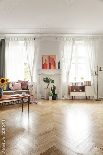 Foto Murales Poster, plants and cupboard in bright loft interior with wooden floor and drapes at windows. Real photo