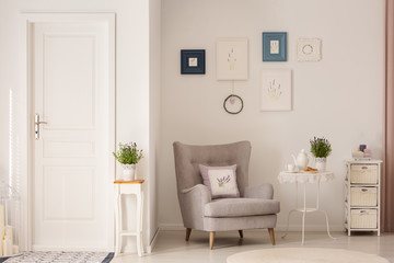 Flowers on table next to grey armchair in white living room interior with posters and door. Real photo