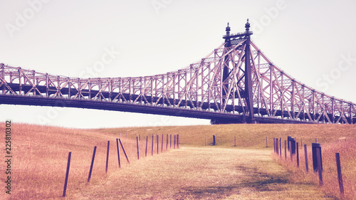 Vintage stylized picture of the Queensboro Bridge seen from Roosevelt Island, New York City, USA. - 225810302