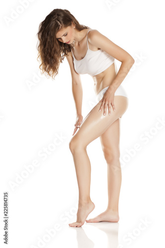 Leinwanddruck Bild Young woman applying cream on her body on white background
