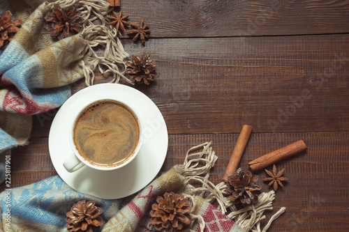 Autumn still life with cup of black coffee, pine cone, cinnamon, warm scarf on wooden board. Copy space. View from above.