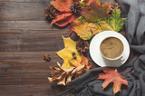 Autumn still life with cup of coffee,pine cone, cinnamon, warm scarf on wooden board. Copy space. Top view.